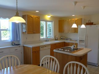 Dennisport house photo - Bright & airy kitchen has dishwasher, side-by-side fridge, oven & island cooktop