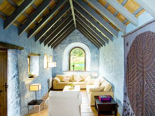 Cortes de la Frontera villa photo - The blue living area with arched window and view of the pool and gardens