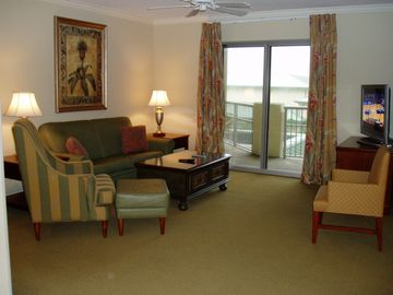 Spacious Living Area with large flat screen TV & entry to balcony.