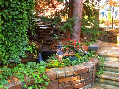 Delightful water feature and lit stone pathway next to the house.