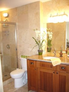 Travertine-tiled bath with walk-in shower