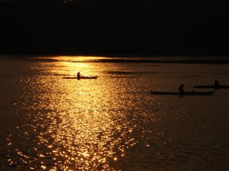 Kayakers enjoying a sunset paddle in front of cottage