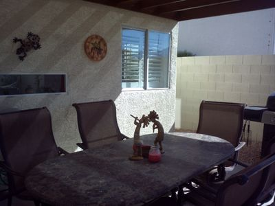 Granite patio table with 6 chairs under fabric-covered pergola