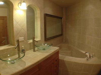 Large custom tile bath tub with beautiful mirrors.