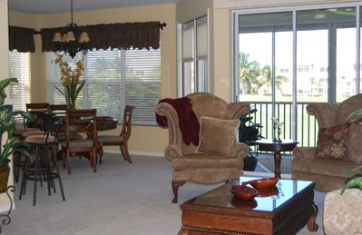 View from living room to dining room, breakfast bar & kitchen around to the left