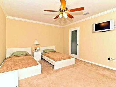 Bedroom highlighted by ceiling fan and wall mounted flat screen TV