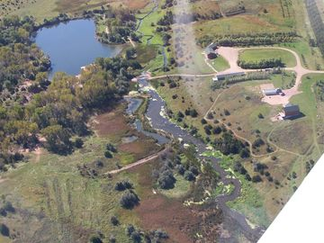 Aerial view of the lodge over looking the lake and small creek.