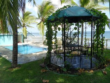 Gazebo in front of pool and ocean on right