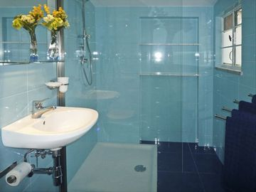 Aquamarine tiles in modern bathroom with large shower.