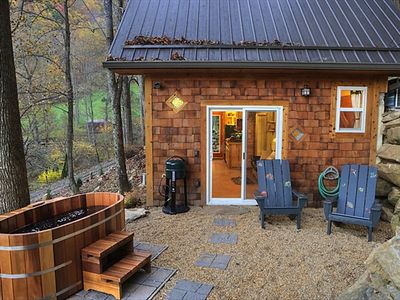 Meadow Branch Cottage front patio at dusk with cedar soak tub and outdoor grill.