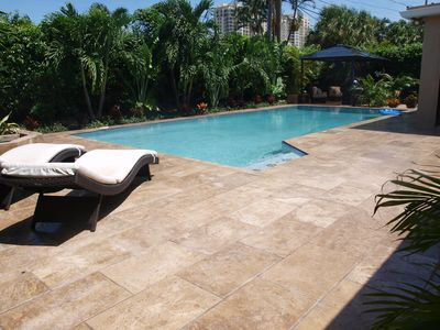 Tropical Resort-style pool setting with travertine tiles and outdoor kitchen.