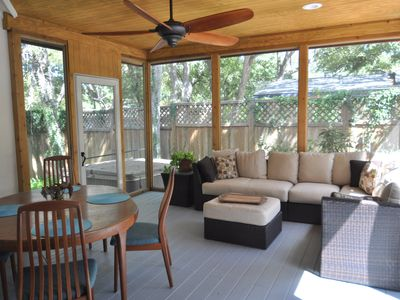 Relax on the screened porch with sectional couch, dining table and ceiling fan.
