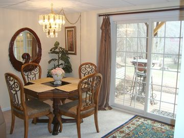 Dining area off the lower level kitchen & media room. Doors lead to lawn & lake