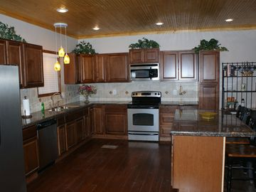 Well equipped kitchen features granite counters and stainless appliances.