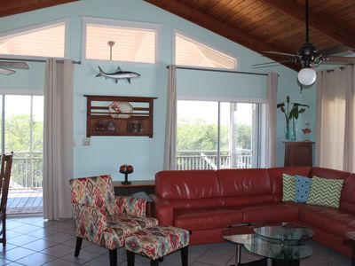 Spacious living room with double sliding doors leading to screened in porch.