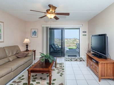 Enjoy our ground floor ocean front living room with HDTV - Island South 4's ground floor condo is ultra cool with sleek, comfortable sofas, a wide, HDTV, and sliders that lead out to the patio and ocean views.