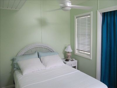 Tranquil main bedroom includes its own air conditioner.