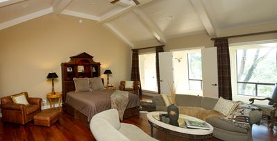 Huge master bedroom with a king bed and plenty of seating.