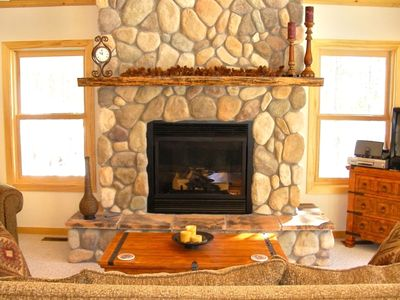 Snuggle up in front of the river rock fireplace