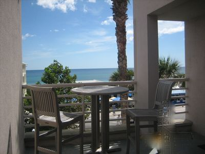 Seaside condo rental - South side of courtyard with bistro table and chairs.