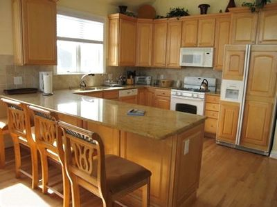 Fully stocked kitchen with granite countertops 4 chair breakfast bar