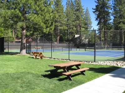 The private facilities include tennis courts and a large grass area.