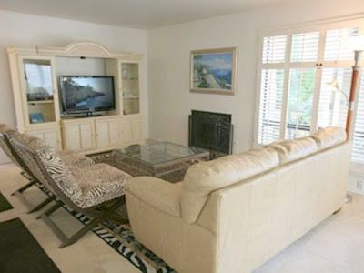 Open living room with comfortable seating and flat screen TV.
