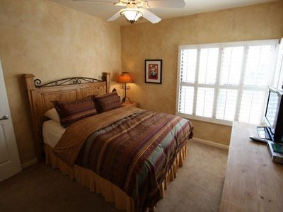 Guest bedroom with a queen bed and flat screen TV