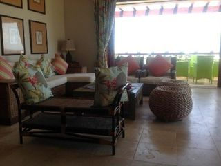 Punta Cana condo photo - Living room. Green chairs/table on second balcony. Wide glass doors to balcony.