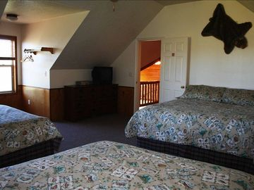 Upstairs room with 1 King bed and 2 Queen beds and a TV with DVD/VHS player