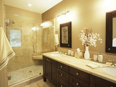 Master bathroom with walk-in shower, travertine walls and countertop.