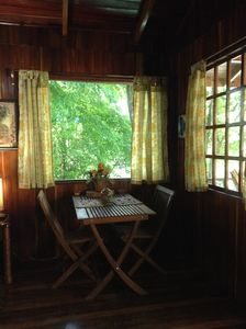 Large windows surround the dining table for viewing the lovely setting