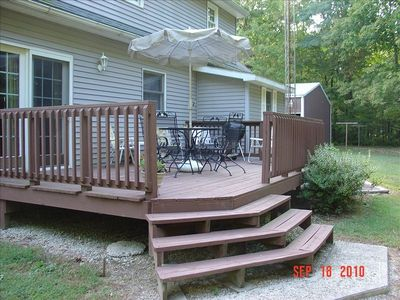 A very large deck complete with a charcoal grill and patio seating.