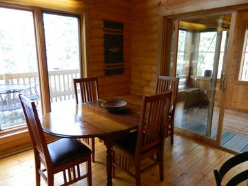 Dining area off kitchen is also open to screened porch which opens to deck
