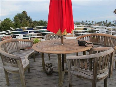 Teak dining set with lounge chairs on roof deck overlooking the ocean