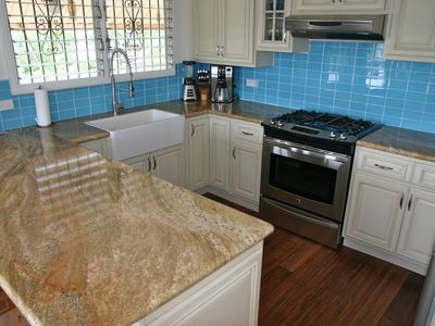 kitchen with gas range, granite counters, dishwasher & farm sink ocean view