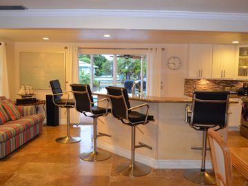 Spacious kitchen island and family room open to outside by pocket panoramic door