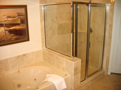 Elegant master bathroom with marble tiles,glass shower, sunken jetted tub.