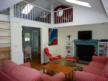 Living room with skylights and ship's ladder to loft opens into kitchen.