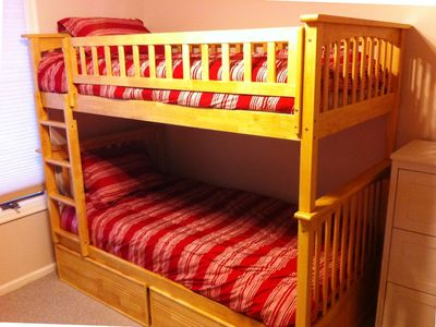 Close up of red bunk beds. Storage drawers beneath.