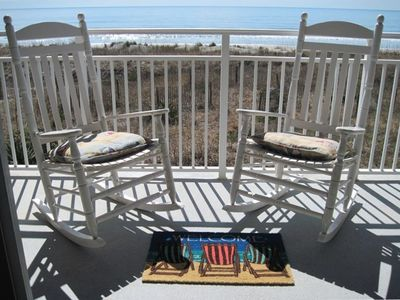 Oceanfront deck off living room with table and 4 chairs and two rockers