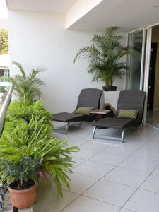 Lushly landscaped private terrace with comfy lounge chairs