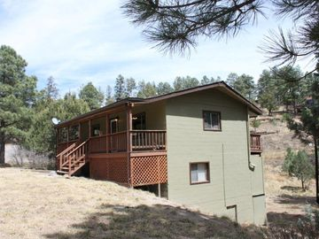 Ruidoso cabin rental - Sierra Vista Lodge's side view and open front yard.