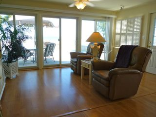 Slaughter Beach house photo - Comfortable furniture with a wall of glass doors to large deck overlooking water