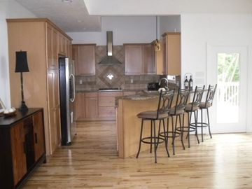 Fully-equipped kitchen with stainless appliances, granite counters, and bar area
