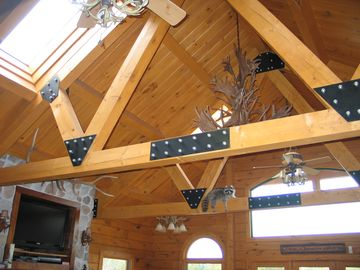 Exposed timber trusses and antler chandelier give this room that rustic feel