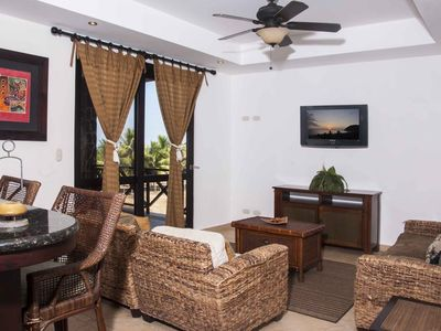 Main living area with flat screen TV and balcony access