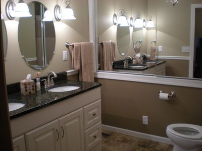 Large bath with tiled shower & bathtub. Two sinks and large storage closet.