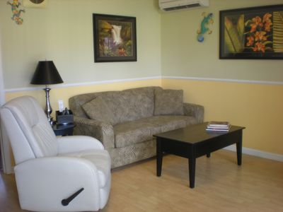 Living area with air conditioner, leather rocker recliner and full sofa sleeper