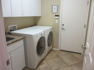 Laundry room with front loading washing machine, dryer, & sink